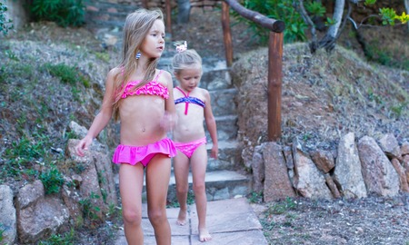 2 persons: Two adorable little girls in swimsuits during the summer holidays