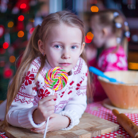 Little girl with candy preparing Christmas cakes photo
