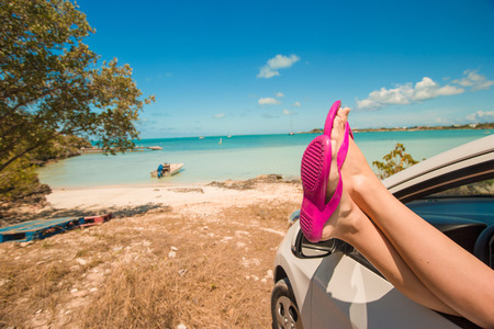 Flip Flops from the window of a car on background tropical beach Stock Photo