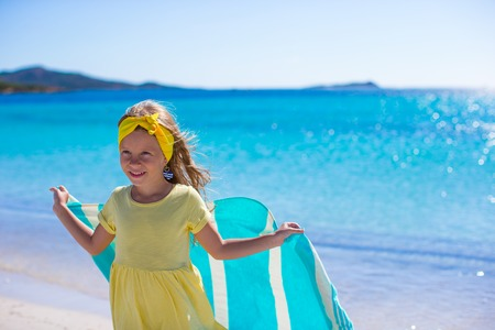 Little girl have fun with beach towel during tropical vacation photo