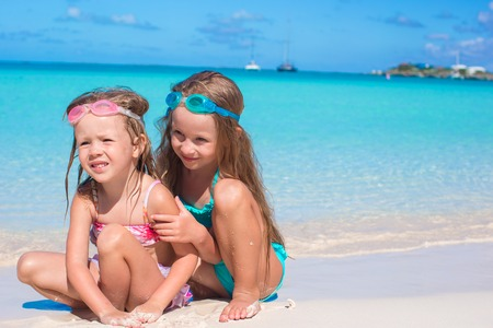 children sandcastle: Adorable little girls in swimsuit and glasses for swimming at beach