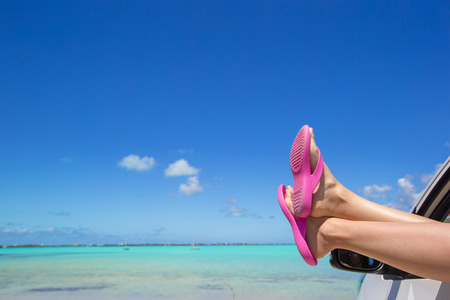 flip flops: Flip Flops from the window of a car on background tropical beach Stock Photo
