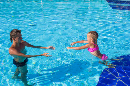 Father and little girl enjoy swimming in the pool photo
