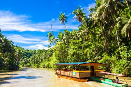 Exotic cruise boat with tourists on jungle river Loboc, Bohol