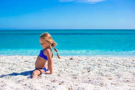 Adorable little sporty girl on white tropical beach photo