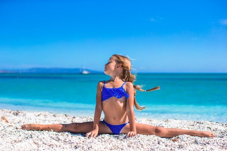Little girl making leg-split on tropical white sandy beach photo