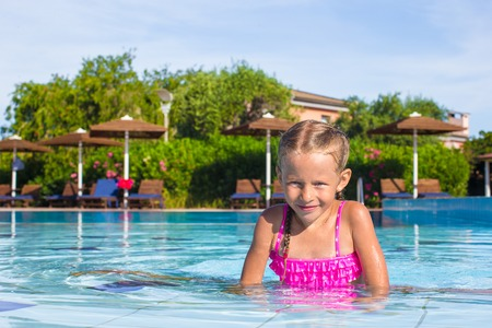 Adorable happy little girl enjoy swimming in the pool photo