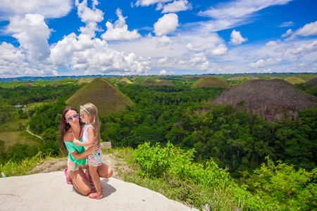 Young mom and adorable little girl at the Chocolate Hills in Bohol photo