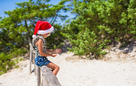 Cute little girl in christmas hat during beach vacation photo