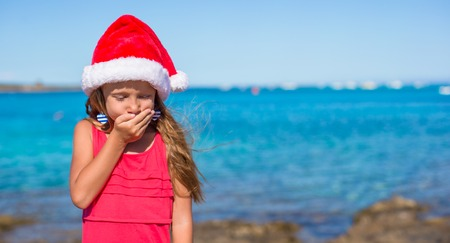 Adorable little girl in santa hat during beach vacation photo