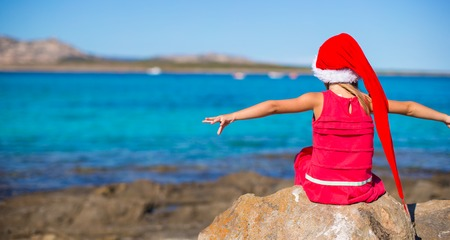 Little girl in red hat santa claus on the beach photo