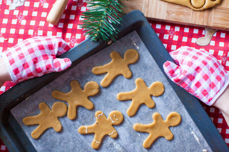 Raw gingerbread men with glaze on baking sheet for Christmas time photo