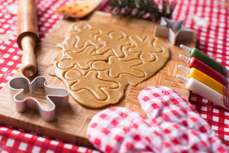dripping pan: Cutting gingerbread cookie dough for Christmas