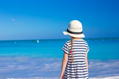 Adorable little girl at white beach during summer vacation photo