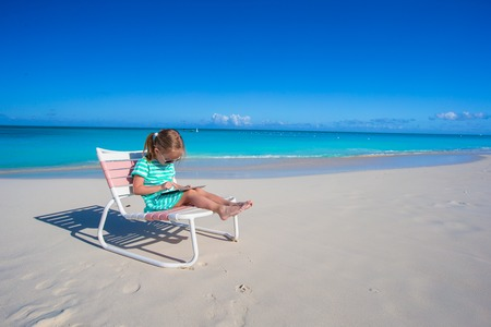 girl with laptop: Little girl with laptop on beach during summer vacation