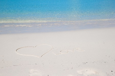 Love written on tropical beach white sand photo