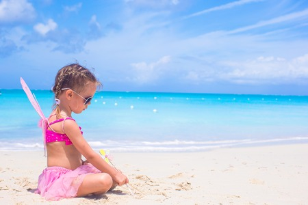 beach butterfly: Adorable little girl with wings like butterfly on beach vacation Stock Photo