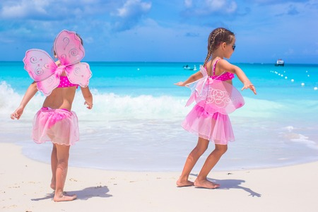 beach butterfly: Little girls with butterfly wings have fun beach summer vacation