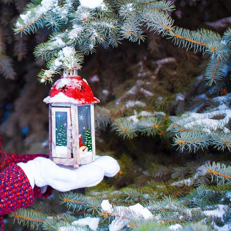 Beautiful red decorative Christmas lantern on warm mittens photo