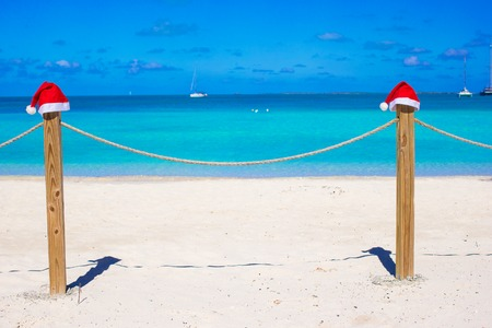 Close-up santa hat on fence on tropical white caribbean beach photo
