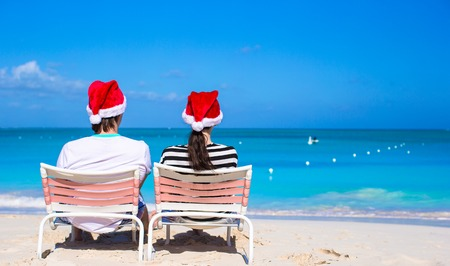 Young happy couple in red Santa hats on tropical beach photo