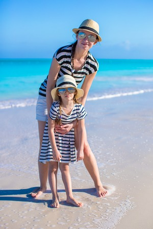 Happy mother and little daughter have fun at tropical beach photo