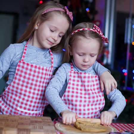 Little girls in mittens baking Christmas gingerbread cookies photo