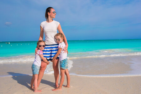 Happy mother and little daughters have fun at tropical beach photo