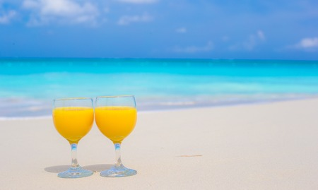 clang: Closeup of two glasses of orange juice on tropical white beach