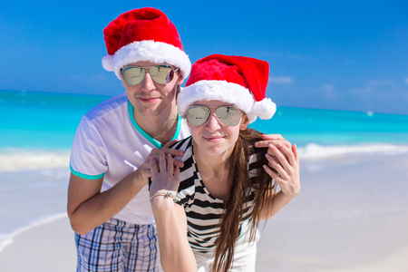 Portrait of young couple in Santa hats enjoy beach vacation photo