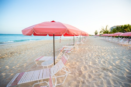 Tropical empty sandy plage with umbrella and beach chair