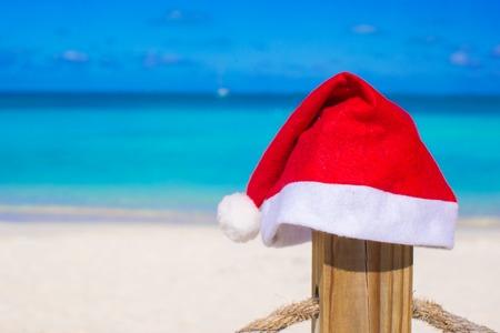Closeup Santa hat on fence at tropical beach photo