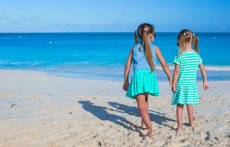 youngbaby: Back view of little girls enjoying summer beach vacation