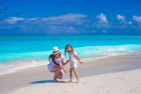 Happy mother and little daughter have fun during tropical beach photo
