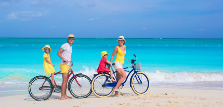 Young family riding bicycles on tropical beach Stock Photo - 34629423