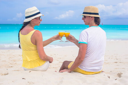 citrus family: Happy couple with glasses of orange juice on tropical beach
