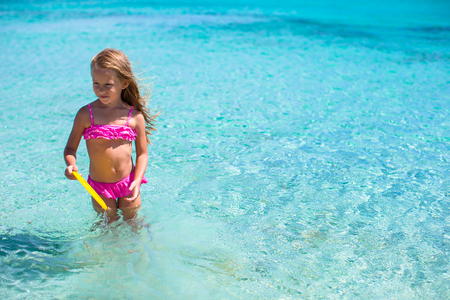 flying disc: Little girl playing flying disc during tropical vacation in the sea