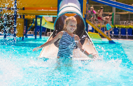 child swimsuit: Little girl on water slide at aquapark during summer holiday