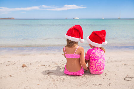 Little adorable girls in Santa hats during beach vacation photo