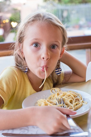 people eating restaurant: Adorable little girl eating spaghetti in outdoors restaraunt
