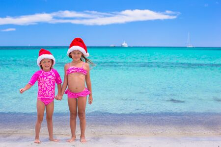 Little girls in Santa hats during summer vacation photo