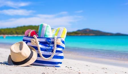Blaue Tasche, Strohhut, Flip Flops und Handtuch auf weißem Strand Standard-Bild - 35296768