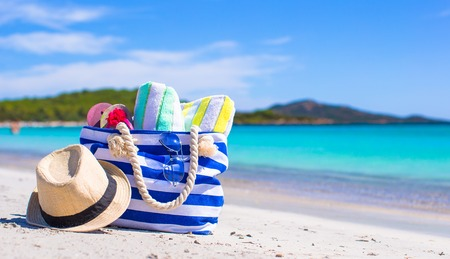 Blue bag, straw hat, flip flops and towel on white beach Stock Photo