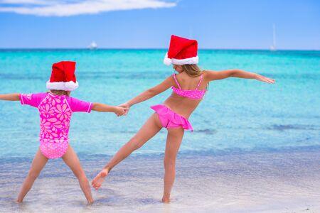 beach hat: Little girls in Santa hats during summer vacation