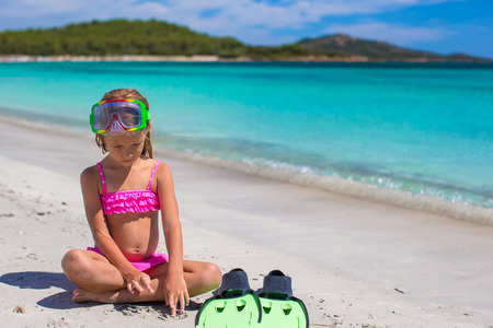 snorkling: Little girl with flippers and goggles for snorkling on white beach