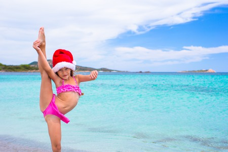 Little adorable girl in red Santa hat at tropical beach Stock Photo