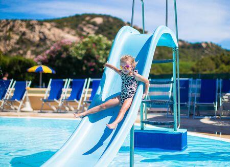 bikini wear: Little girl on water slide at aquapark on summer holiday