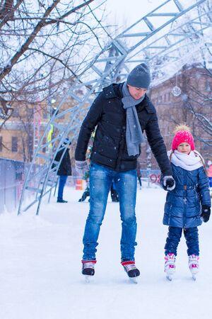 patinaje sobre hielo: Padre joven y adorable ni�a en pista de patinaje al aire libre Foto de archivo