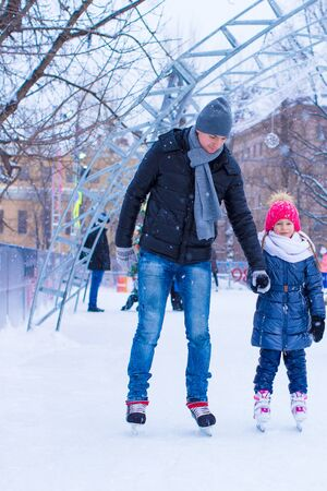 ice rink: Young father and adorable little girl on skating rink outdoor