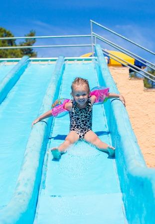 bikini wear: Child on water slide at aquapark during summer holiday
